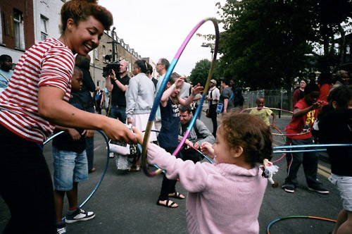 Photo of Marawa teaching kids hoola hooping in the street.