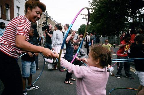 Photo of Marawa teaching kids hoola hooping in the street.